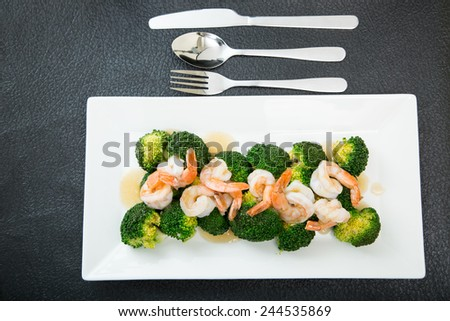 Gravy and Shrimp with broccoli on white dish - stock photo