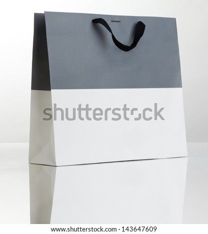 Gray and white shopping bag on white with reflection. - stock photo