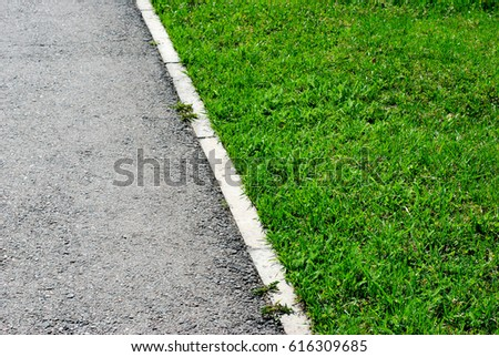 Gray asphalt and green grass border in perspective