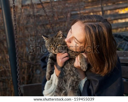 gray cat in the hands of a young girl - stock photo