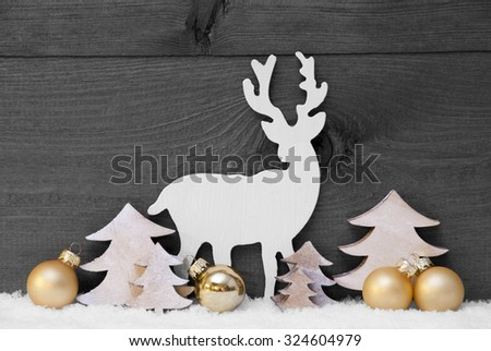 Gray Christmas Card With Golden Festive Decoration On Snow. White Reindeer, Christmas Ball, Tree. Brown, Rustic, Vintage Wooden Background. Copy Space For Advertisement. Black And White - stock photo