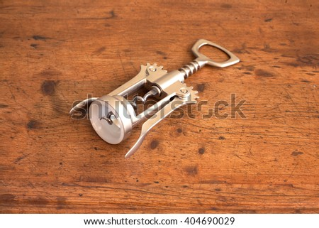 Gray corkscrew on wooden background side view closeup. Tool for pulling out wine corks
