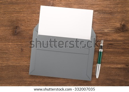Gray envelope with white paper and pen on a table