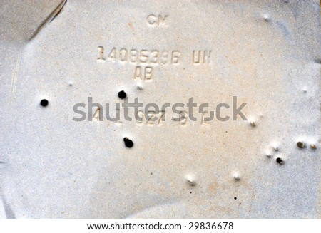 Gray, grungy piece of old metal with random numbers and letters, riddles with bullet holes. - stock photo