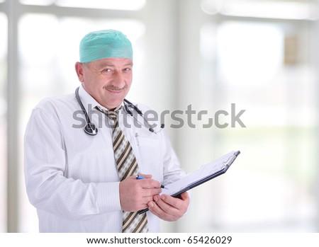 gray hair expertise handsome senior doctor hospital portrait white corridor, writing receipt - stock photo