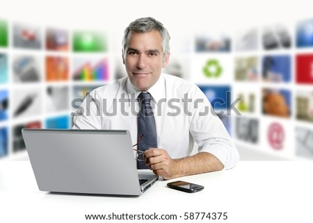 gray hair tv news screen presenter laptop smiling white desk - stock photo