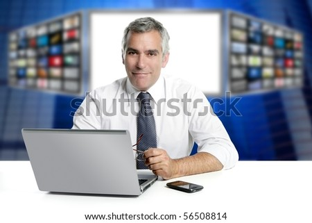 gray hair tv news screen presenter laptop smiling white desk [Photo Illustration] - stock photo