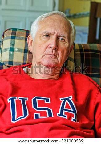 Gray haired caucasian senior man relaxing in easy chair. - stock photo