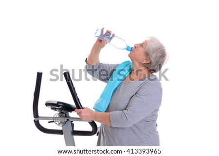 gray-haired female senior train with fitness machine and drinking water - stock photo