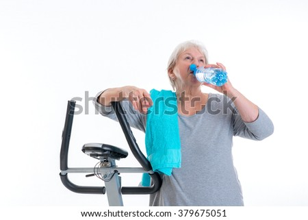 gray-haired female senior with water bottle train with fitness machine - stock photo