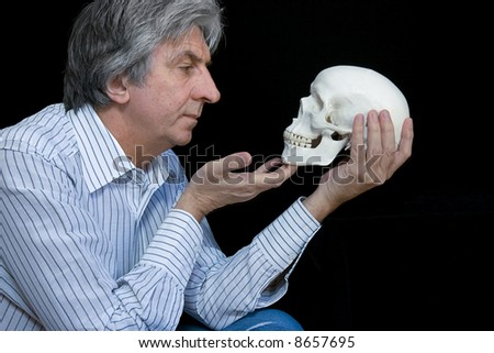 Gray haired man looking at a skull - stock photo