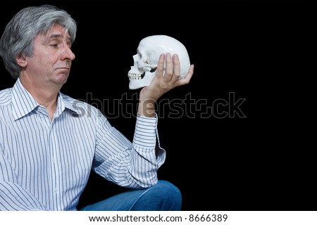 Gray haired man staring at a skull - stock photo