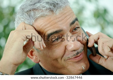 Gray haired mature businessman calling on mobile phone, smiling.