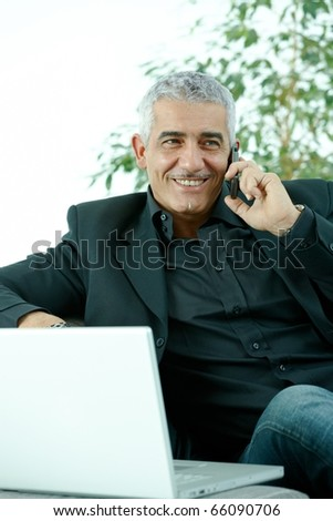 Gray haired mature businessman sitting on couch working on laptop computertalking on mobile phone, happy, smiling.? - stock photo
