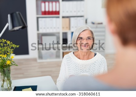 Gray Haired Senior Businesswoman Listening to her Subordinate Talking to her with Happy Facial Expression. - stock photo