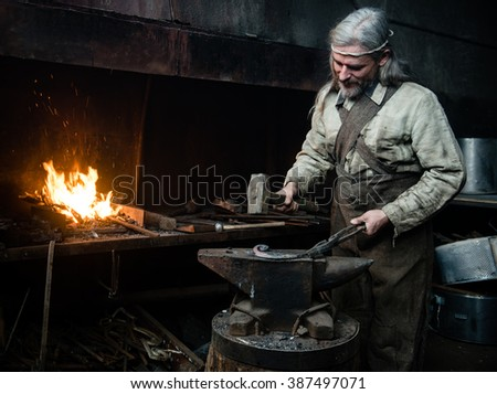 Gray-haired smith forges detail in the smithy - stock photo
