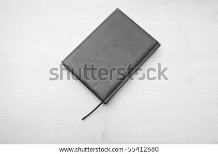 Gray leather diary book laying on wooden table - stock photo