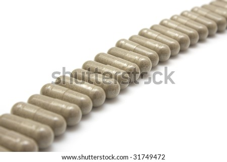 gray medical pills in a row on white background - stock photo