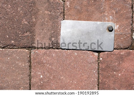 Gray metal label with bolt on a old brown wall - stock photo