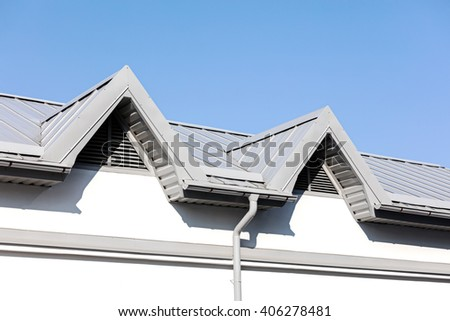 gray metal roof with newly installed rain gutter system - stock photo