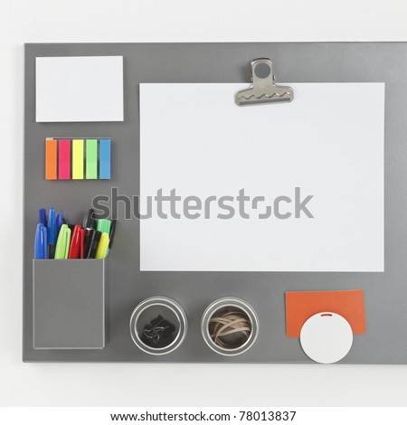Gray metallic magnetic board with blank paper sheet held by a magnetic clip - stock photo