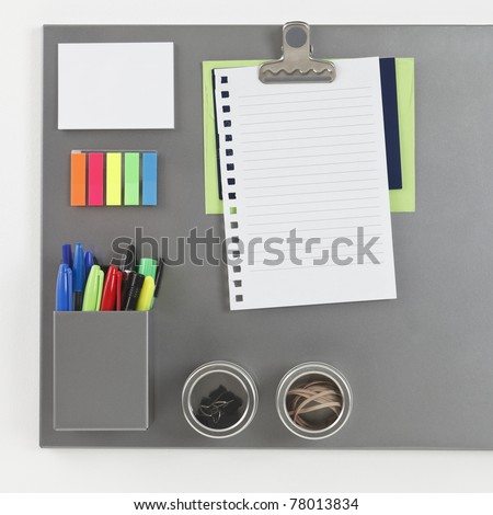 Gray metallic magnetic board with blank piece of paper held by a magnetic clip - stock photo