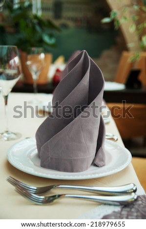 gray napkin on table in restaurant, tableware - stock photo