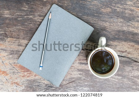 gray note book with coffee cup on grunge wood - stock photo