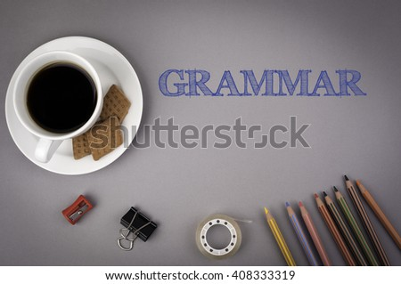 Gray office desk with the inscription - Grammar  - stock photo