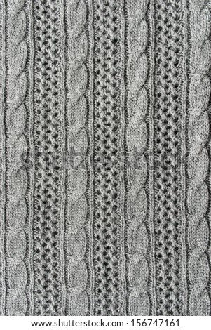 Gray openwork wool knitting with vertical strips as a background - stock photo