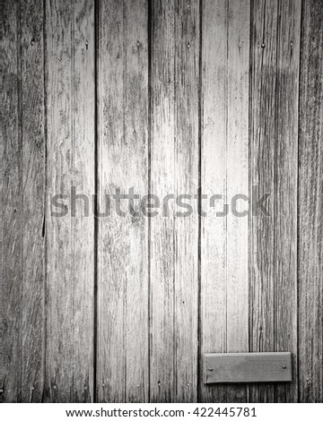 gray plank with small blank sign for text - stock photo