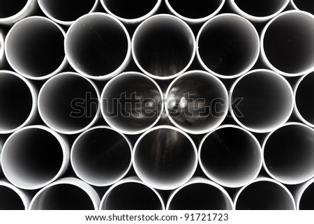 gray PVC tubes plastic pipes stacked in rows pattern - stock photo