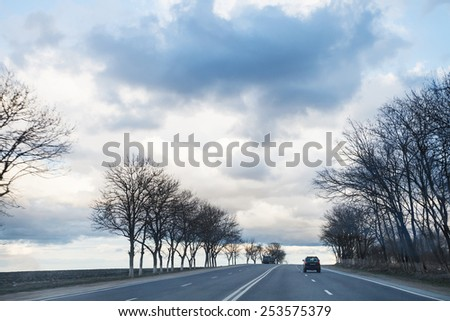 gray rainy clouds over highway in early spring evening - stock photo