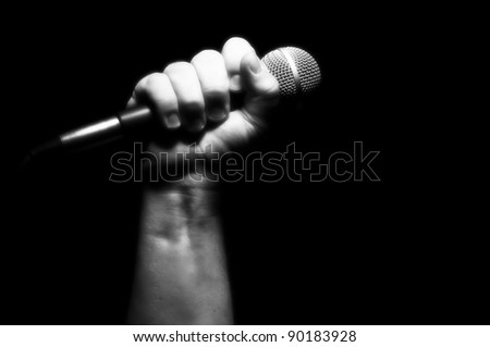 Gray Scale Microphone Clinched Firmly in Male Fist on a Black Background. - stock photo