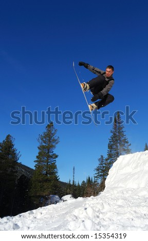 Gray snowboarder jumping high in the air - stock photo