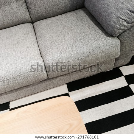 Gray sofa and wooden coffee table on striped carpet. - stock photo