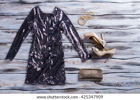 Gray sparkly dress and shoes. Beige glossy heels and dress. Lady's luxury evening outfit. Stylish apparel sold at boutique. - stock photo