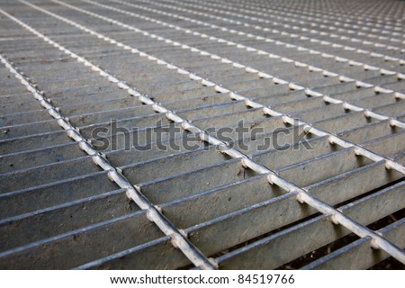 Gray steel grating image taken low to the ground for a long diminished perspective - stock photo