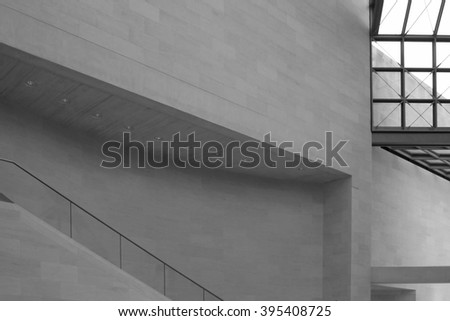 Gray stone wall and part of staircase. Refined abstract fragment of contemporary architecture without noticeable / unique elements. Modern interior detail in light beige and gray colors. - stock photo
