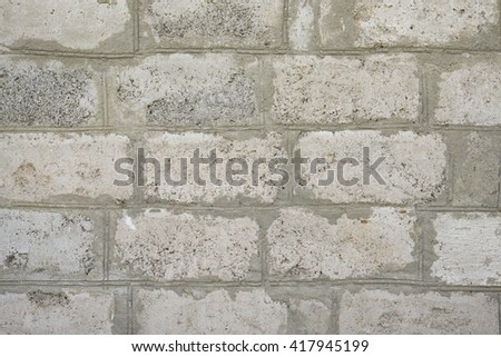 gray stone wall . hewn stones bright . masonry cement. white brick masonry