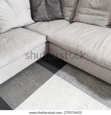 Gray textile corner sofa and carpet. Modern furniture. - stock photo