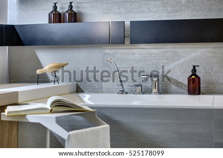 Gray tiled bathroom with black shelves on the wall. There is a bath with chrome shower and faucet, pump bottles, stand with a towel and a book, rack with a decorative wooden bird. Closeup. Horizontal.