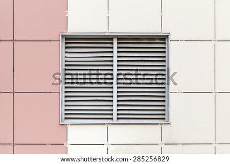 Gray ventilation grille on the window, modern industrial building facade fragment - stock photo