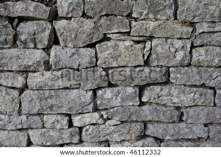 Gray wall of old uneven stones, horizontal - stock photo