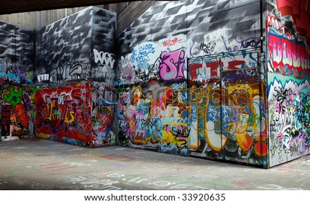 Gray walls painted with bright colorful graffiti - stock photo