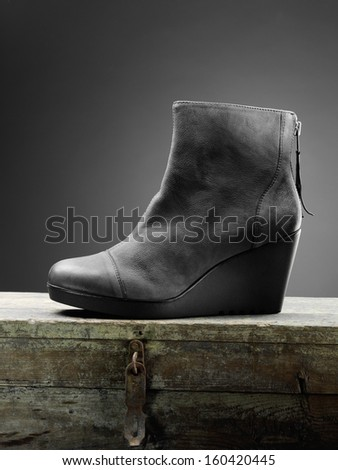 gray woman boots on the wooden box  - stock photo