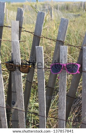 Gray wood and wire sand dune fence wearing lost sunglasses - stock photo