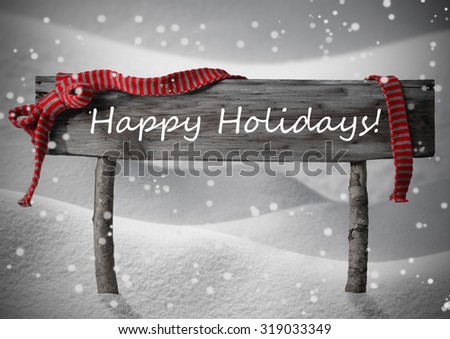 Gray Wooden Christmas Sign On White Snow. Snowy Scenery, Snowflakes. Red Ribbon, English Text Happy Holidays. Christmas Decoration Or Christmas Card. Rustic Or Vintage Syle.Black And White Image - stock photo