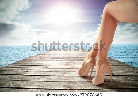 gray wooden pier on ocean and long woman legs