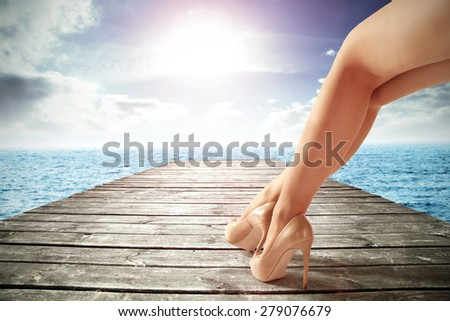 gray wooden pier on ocean and woman and shoes